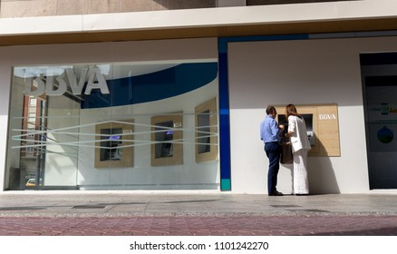 CASTELLON, SPAIN - OCTOBER 2017: A couple takes money from an ATM in the new offices of the BBVA bank in the center of the city.