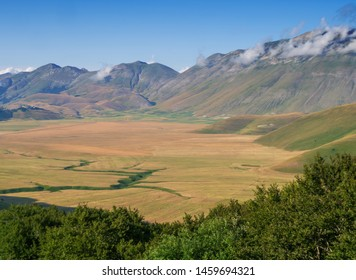 Castelluccio di Norcia, in Umbria, Italy. Fields and hills, Apennines behind, sunny day. Colourful landscape view across the valley, plain.