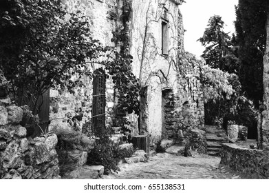 """Castelnou (France) Narrow streets of medieval village classified among """"the most beautiful villages in France"""" decorated with blooming wisteria. Black and white."""