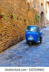 Castiglione della Pescaia, Tuscany 01.08.2018. Old vintage Ape car on Medieval alley in the village of Castiglione della Pescaia (Grosseto) with old historical buildings. Italy