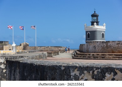 CASTILLO DE SAN FELIPE DEL MORRO, PUERTO RICO, USA - FEB 16, 2015: Lighthouse Tower and stone walkway at fortress lined with flags of United States and Puerto Rico and Cross of Burgundy