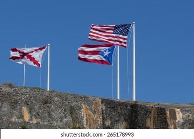 CASTILLO DE SAN FELIPE DEL MORRO, PUERTO RICO, USA - FEB 16, 2015: Visitors walk across a stone bridge toward a square opening decorated with a ornate white crest that is the entrance of the fortress.