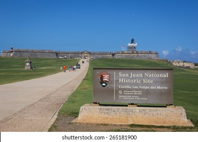 CASTILLO DE SAN FELIPE DEL MORRO, PUERTO RICO, USA - FEB 16: Front view of fortress with official sign San Juan National Historic Site in foreground and stone fortress and lighthouse in background