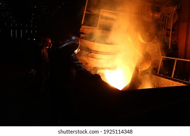 Casting iron molten metal into the sand mold.