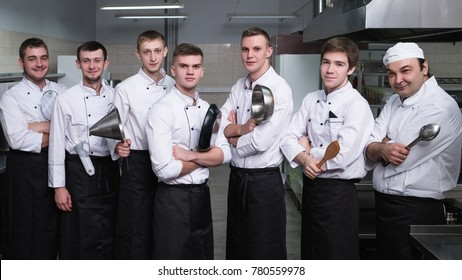 Casting process to find the best for a cooking competition. Male cooks stand confident with kitchen utensils in their arms. Dream of being a chef comes true