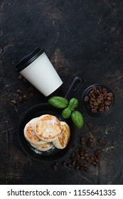 Cast-iron frying pan with cottage cheese pancakes and coffee, flatlay over dark brown stone background with copy space