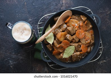 Cast-iron pan with traditional Irish meal of beef and beer stew, dark brown stone background, top view, studio shot