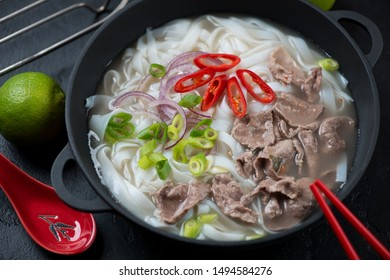 Cast-iron pan with vietnamese traditional pho bo soup, close-up, studio shot