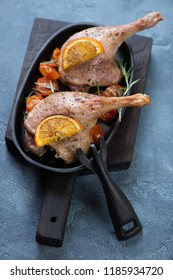 Cast-iron serving pan with baked duck legs on a black wooden cutting board, vertical shot over blue stone background