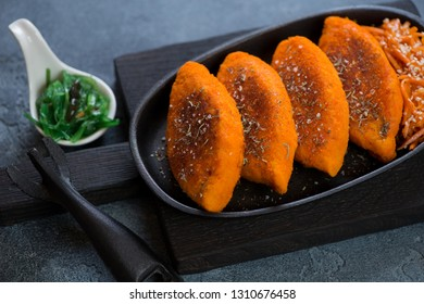 Cast-iron serving pan with fried carrot cutlets on a black wooden cutting board, horizontal shot
