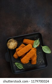 Cast-iron serving pan with roasted fish fingers, lemon and green basil. Flatlay on a dark brown metal surface with space, vertical shot