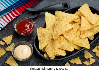 Cast-iron serving tray with nachos chips and dipping sauces, studio shot over grey stone background