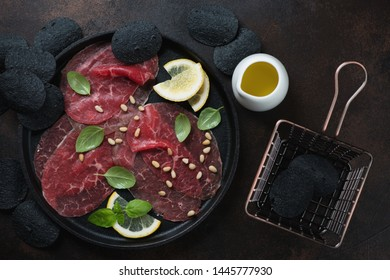 Cast-iron tray with carpaccio beef and black potato chips, flatlay over dark brown metal background