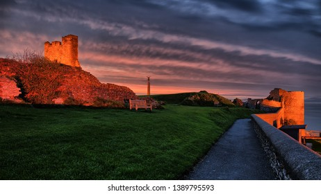 The Castle of Aberystwyth after sunset with a beautiful orange and purple evening sky.