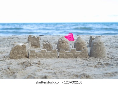 The castle is built from the sand on the beach with blurred seascape and blue sky in background