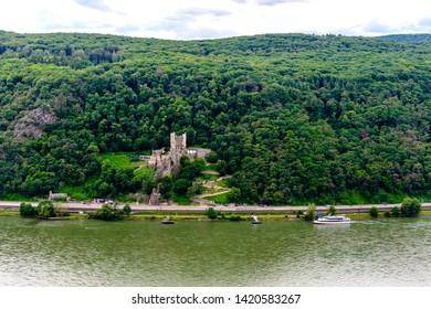 Castle Burg Rheinstein with a ship by Assmanshausen in the upper middle Rhine river valley (Mittelrhein), nearby Rudesheim, Bingen. Assmanshausen, Hessen, Germany. Unesco
