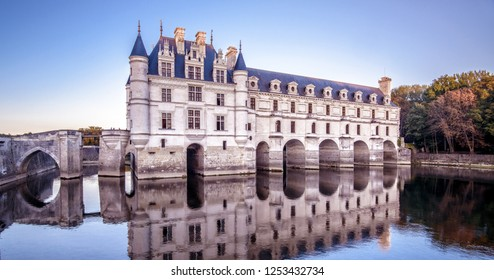 Castle or chateau de Chenonceau at sunset, France. This Renaissance castle is one of the main landmarks in France. Panoramic view of the old castle on a river. Magnificent French castle in evening.
