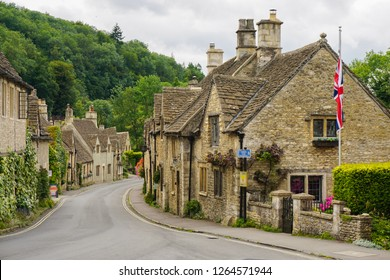 Castle Combe village in Cotswolds, UK - small medieval houses aligned along the road - summer day