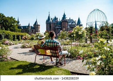 Castle de Haar Netherlands Utrecht on a bright, young couple men and woman mid age walking in the castle garden