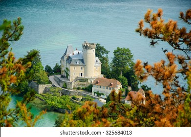 Castle of Duingt at Annecy Lake (known as Europe's cleanest lake). Haute-Savoie, France. View from above through pine twigs. Selective focus on the castle.