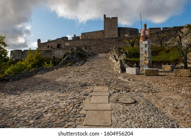 Marvão castle entrance with cobblestone road, blue sky with white clouds