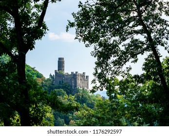 Castle Maus framed by trees along the Rhine River in Germany