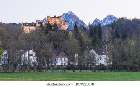 Castle up in the mountains above residential houses in Bavaria, south of Germany