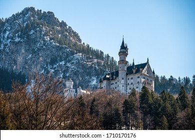 Castle of Neuschwanstein from the city of Hohenschwangau with blue sky and snow-covered rocks