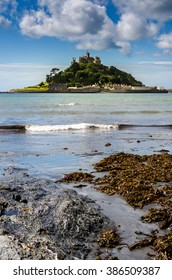 Castle on a island vertical. St Michael's Mount in Cornwall UK at high tide on summer day.