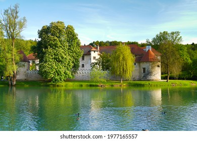 Castle Otočec on the river Krka in southern Slovenia, evening sunset scene with reflection of castle on the water