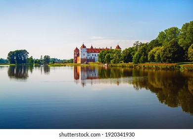 Castle on the shore of the lake. Summer landscape. Ancient medieval fortress. Architectural monument of the middle ages - Mir Castle, Belarus