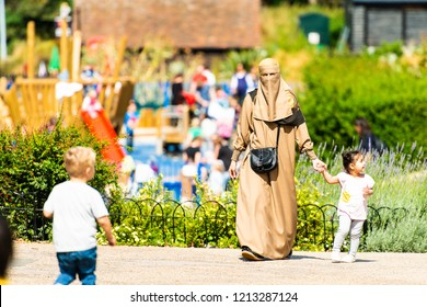 Castle Park, Colchester, Essex - 1st August 2018 - A muslim women in a burkha, hijab walking with her child in Colchester castle park, essex, Culture, religion, multiculturalism