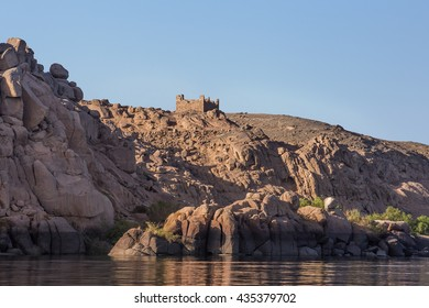 castle rock cliff water. Rocks and stones near the island of Philae at Aswan, Egypt.