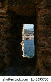 Castle ruin wall with loophole and cannons in the historical port of Alanya
