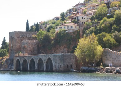 Castle ruin wall with old boat warhouse facilities in the historical port of Alanya