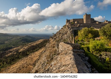 Marvão castle sitting on top of the mountain with valley in the background, with blue sky and white clouds