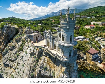 Castle Swallow's Nest on the rock over the Black Sea close-up, Crimea, Russia. It is a tourist attraction of Crimea. Amazing aerial view of the Crimea coast with the castle above abyss on sunny day.