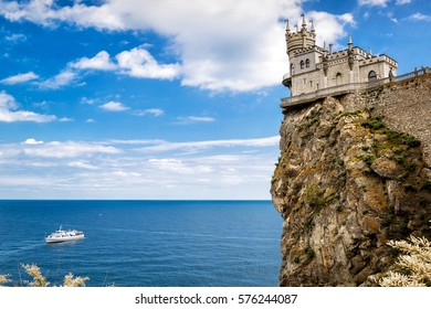 Castle of Swallow's Nest on a rock, Crimea, Russia. Beautiful scenic view of Swallow's Nest at the precipice. Tourist ship sails in Black Sea under the Swallow's Nest. Amazing panorama with castle.