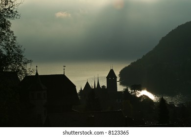 A castle tower silhouetted against a shimmering lake in the early morning