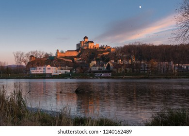 A castle Trencin with a city and a river Vah at sunset