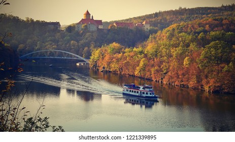 Castle Veveri - City of Brno, Czech Republic - Europe. Beautiful autumn landscape with castle. Brno dam with boat and sunset at the golden hour. Autumn season October.