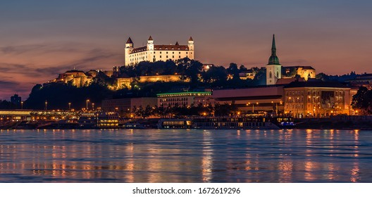 Castle view and cityscape in Bratislava from Danube river after sunset