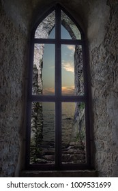 Castle window overlooking the sea. In the background is the sea and the sunset.