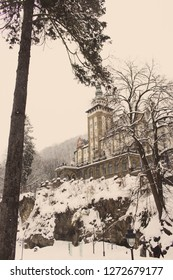 Castle in winter forest in Lillafured, Miskolc, Hungary. Snowy forest and rocks around historical luxury palace. Travel and winter vacation in Europe. Hungarian architecture. Lillafred landmark.