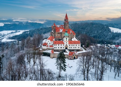 Castle in winter. Romantic fairytale castle in picturesque highland landscape, covered in snow. Castle with white church, high towers, red roofs, stone walls. Bouzov castle, Czech republic.