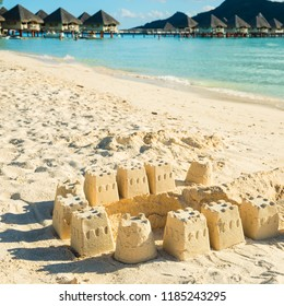 Castles on beach with overwater bungalows at distance