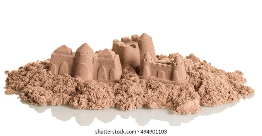 Castles in the sand close up isolated on white background.