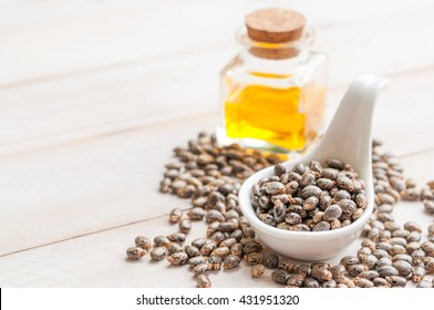 Castor oil with beans on wooden surface