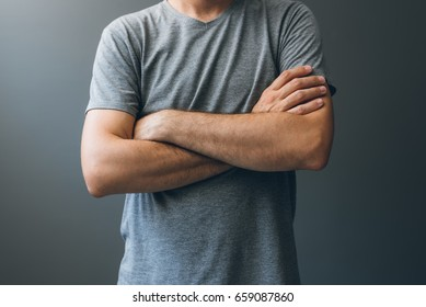 Casual adult man with arms crossed, body language for stress relief, masking insecurities, anxiety and fear as well as self restraint or frustration