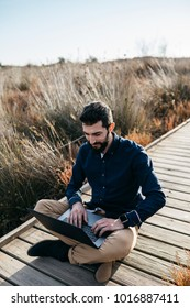Casual adult man enjoying freedom in sunny field using laptop while sitting on wooden pier.